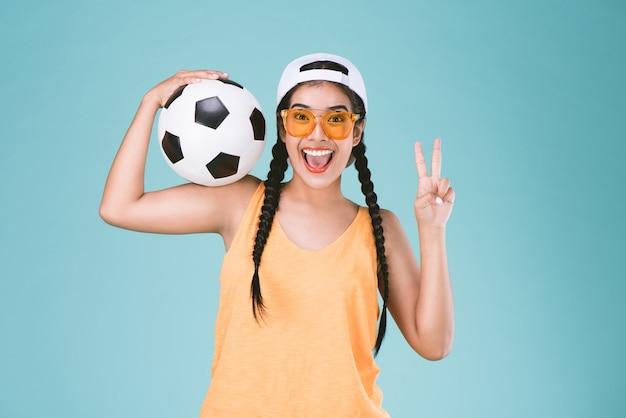 Sport vrouw fan houdt een voetbal, vieren punt twee vinger op tweede teken