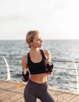 Sport vrouw kickbokser met verbonden handen in pleisters en springtouw poseren