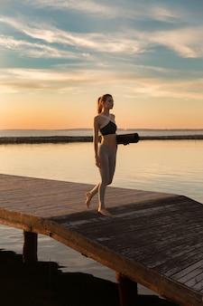 Sport vrouw op het strand met tapijt.