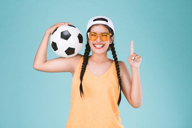 Sport vrouw ventilator die een voetbal, vieren punt een vinger op winnaar teken
