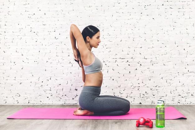 Sport vrouw zittend ontspannen op roze mat en fitness oefening met fles water thuis doen