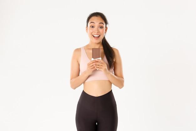 Sport, welzijn en actief levensstijlconcept. gelukkig lachende aziatische vrouwelijke atleet die chocolade-eiwit slecht houdt en er opgewonden uitziet, gezonde snoepjes eet voor langdurige training.