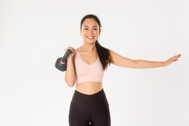 Sport, welzijn en actief levensstijlconcept. glimlachend mooi aziatisch fitnessmeisje, sportschoolcoach strekt een hand uit en tilt kettlebell, bodybuilding, spierkracht op, staande witte muur.