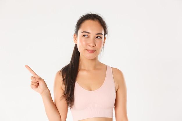 Sport, welzijn en actief levensstijlconcept. sluwe en doordachte glimlachende aziatische sportvrouw, fitness meisje maakt haar keuze, kijkt tevreden met geïntrigeerde glimlach, wijzende linkerbovenhoek.