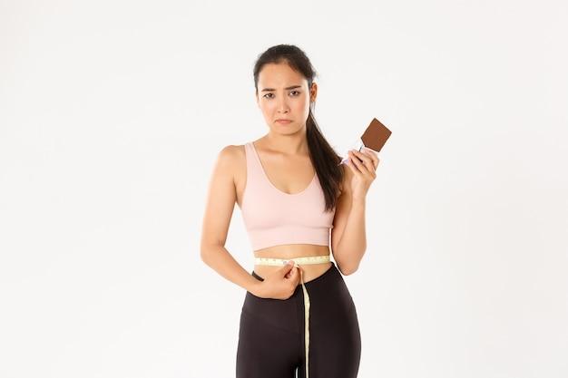 Sport, welzijn en actief levensstijlconcept. teleurgesteld somber aziatisch meisje dat taille met meetlint meet en mokkend omdat ze geen chocoladereep kan eten terwijl ze afvallen op dieet.
