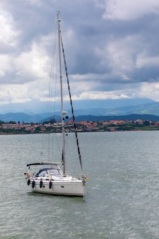 Sport zeilboot afgemeerd in baai met kalme zee en dreigende hemel