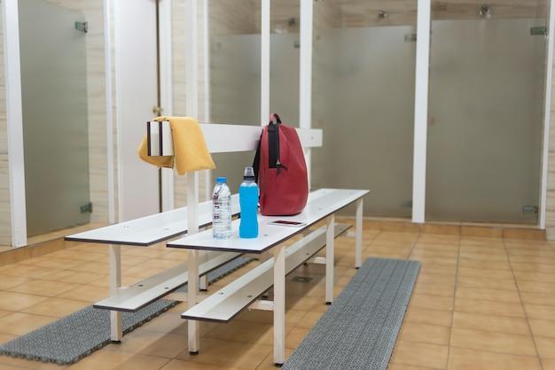 Sportbenodigdheden op een houten bank in een sportschool kleedkamer