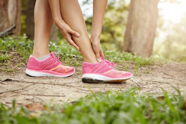 Sportblessure. vrouwelijke atleet jogger die roze sneakers draagt die haar gedraaide of verstuikte enkel aanraken tijdens het joggen of buiten hardlopen.