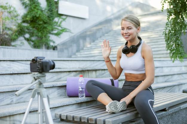 Sportblog. aantrekkelijke jonge sportvrouw begroet haar volgelingen buitenshuis, registreert op camera op statief. les voor haar fitnessvlog