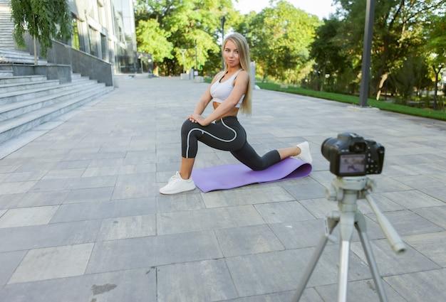 Sportblog. aantrekkelijke jonge sportvrouw die buiten traint, oefeningen demonstreert voor haar online blog, records op camera op statief. les voor haar fitnessvlog