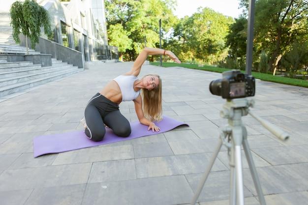 Sportblog. aantrekkelijke jonge sportvrouw die het lichaam buiten uitrekt, oefeningen voor haar blog demonstreert, records op camera op statief. les voor haar fitnessvlog