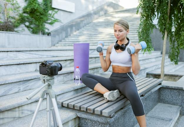 Sportblog. aantrekkelijke jonge sportvrouw die met dumbbells buiten traint, oefeningen voor haar blog demonstreert, records op camera op statief. les voor haar fitnessvlog