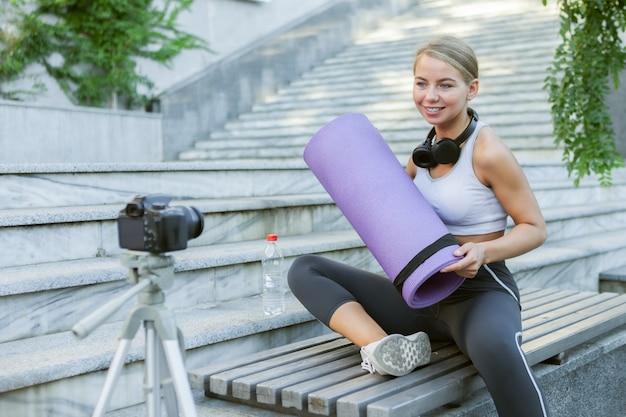 Sportblog. aantrekkelijke jonge sportvrouw traint met yogamat buitenshuis, registreert op camera op statief. les voor haar fitnessvlog