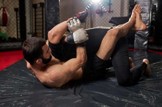 Sportconcept vechten zonder regels. twee atleet worstelaars op sportschool, samen trainen. vecht zonder boksregels mma. sportieve gevechten zijaanzicht