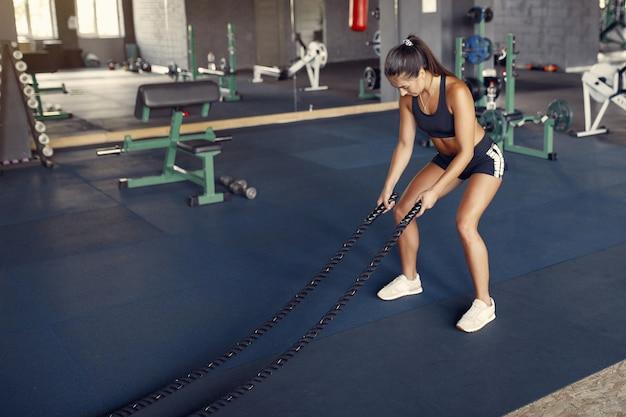 Sporten donkerbruine vrouw in sportkleding opleiding in een gymnastiek