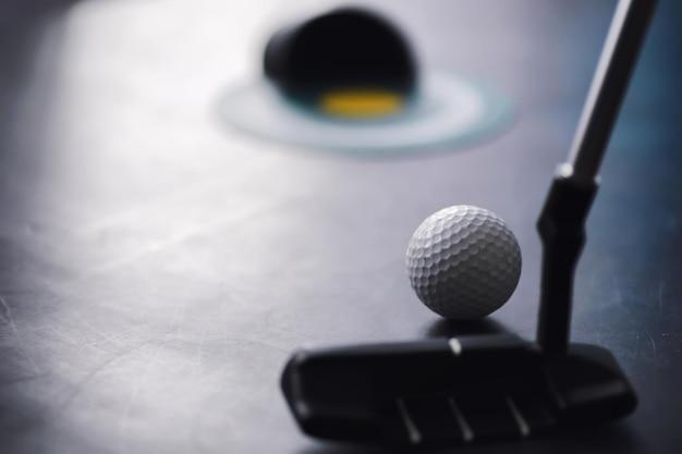 Sporten en een gezonde levensstijl. minigolf. witte golfbal en set voor minigolf op tafel. sportachtergrond met golfconcept.