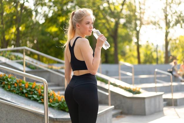 Sporten en fitnessen. jonge blanke vrouw gekleed sportkleding staande buiten water drinken plastic fles zomer park zonlicht achtergrond rusten na de opleiding joggen hardloopoefeningen