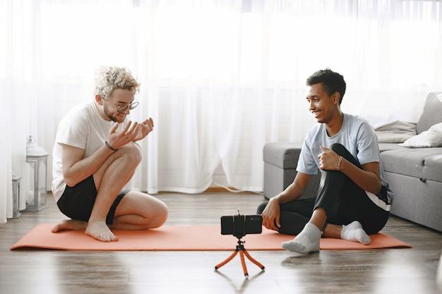 Sporten en gezond leven. fitnesstrainer en stagiair praten op fitness mat. de mannen zitten op de grond en filmen blog.
