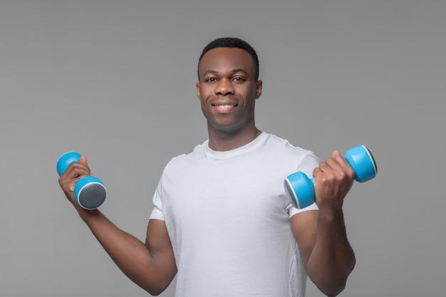 Sporten, halters. glimlachende jonge volwassen sportieve afrikaanse amerikaan in witte t-shirt die zich met domoren in handen bevindt