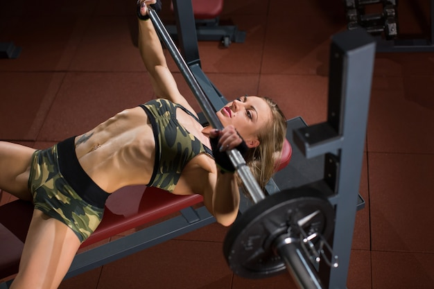 Sporten jonge vrouw die oefeningen met barbell op bankje in de sportschool. bar bench press.