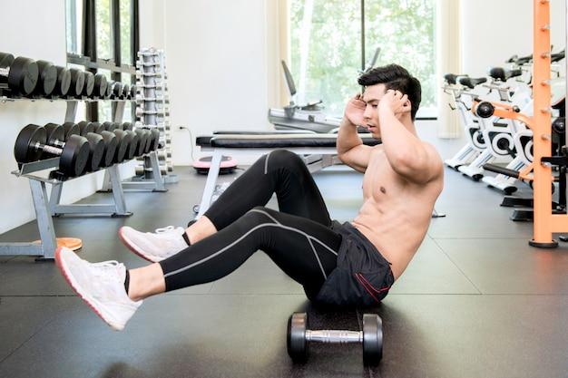 Sporten man fiets crunch training doen op gymnasium