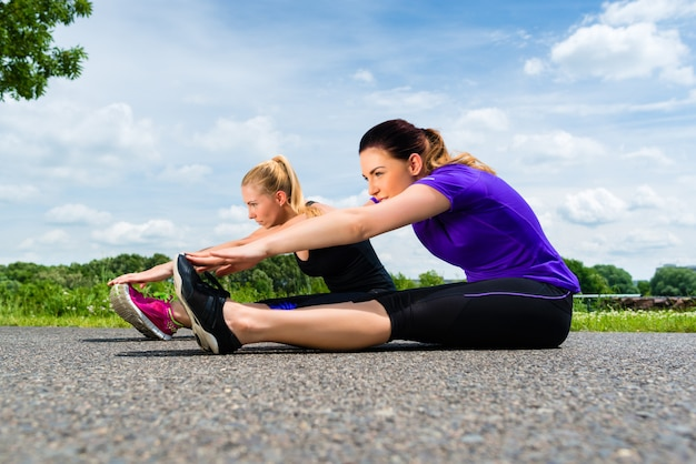 Sporten openlucht - jonge vrouwen die fitness in park doen