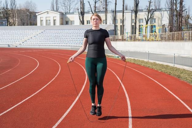 Sporten, sporten in de natuur. vrouw springtouw in het stadion.