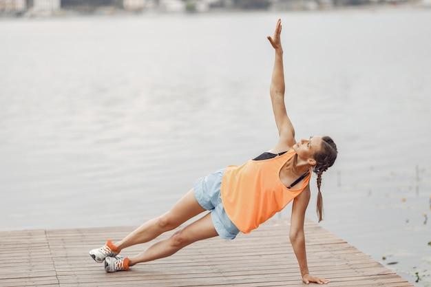 Sportenmeisje aan het water. vrouw in een zomerpark. dame in oranje sportkleding.