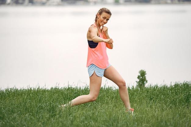 Sportenmeisje aan het water. vrouw in een zomerpark. dame in roze sportkleding.