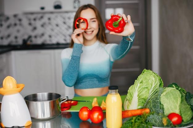 Sportenmeisje in een keuken met groenten