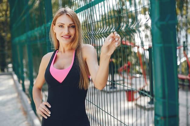 Sportenmeisje in een park van de ochtendzomer