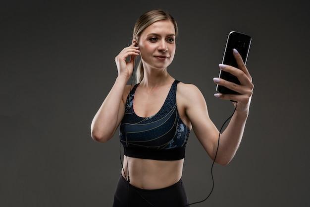 Sportenmeisje in een sportenbovenkant met een telefoon en hoofdtelefoons op een zwarte achtergrond