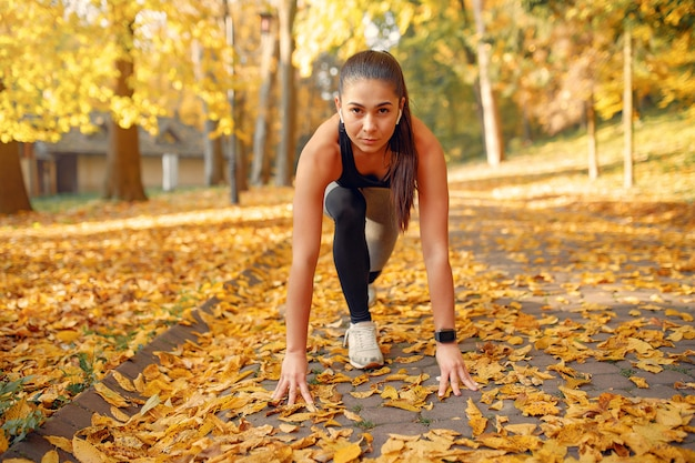 Sportenmeisje in een zwarte bovenkant die in een de herfstpark opleiden