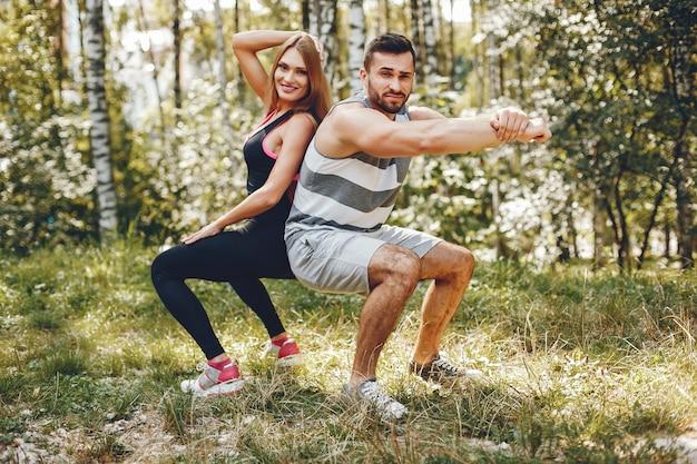 Sportenpaar in een park van de ochtendzomer