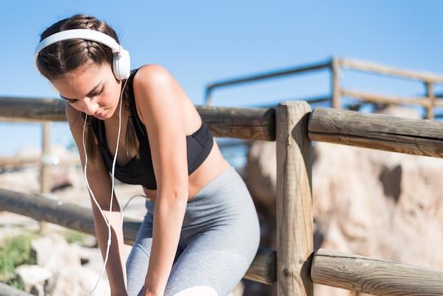 Sportenvrouw die na het runnen van jogging in een park rusten openlucht