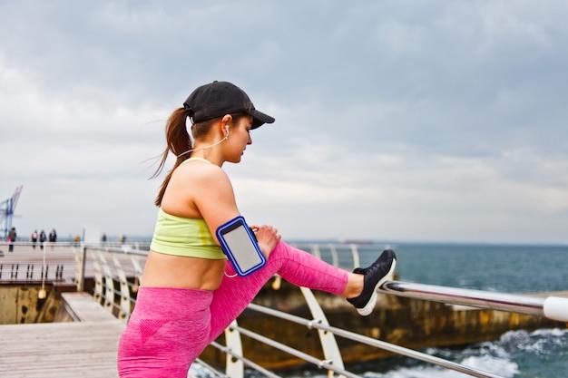 Sportenvrouw in sportkleding met hoofdtelefoons in de oren die uitrekkend been doen alvorens op het strand openlucht op te leiden