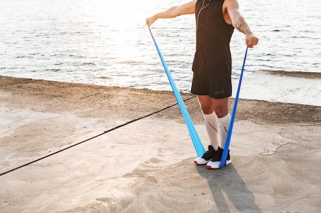 Sporters buiten op het strand maken sportoefeningen met apparatuur.