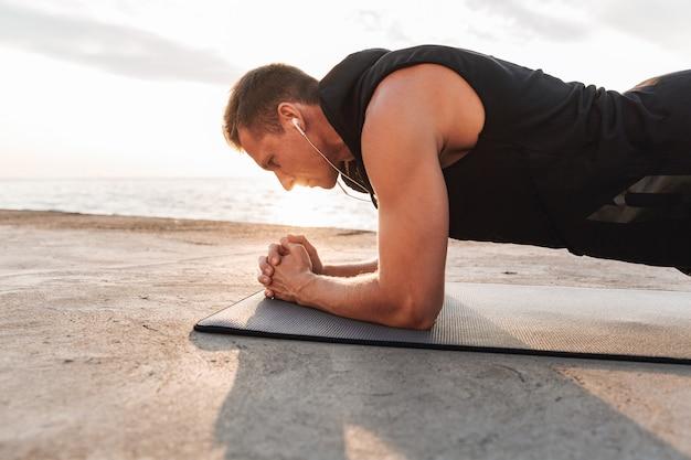 Sporters buiten op het strand maken sportoefeningen.
