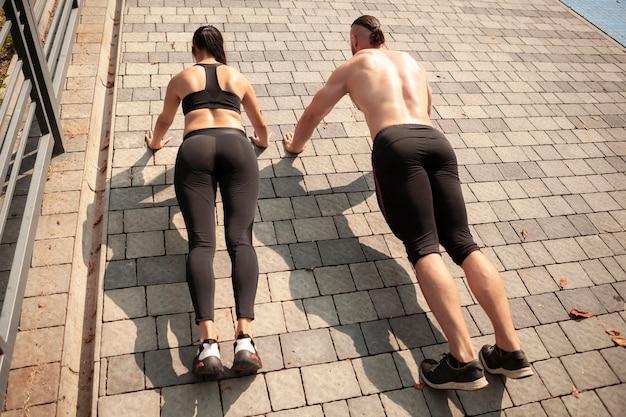 Sporters die vanuit een hoge hoek push-ups doen