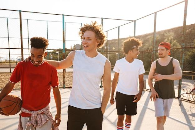 Sporters glimlachend en bal vasthouden terwijl staande op basketbal speeltuin buiten, tijdens zonnige zomerdag