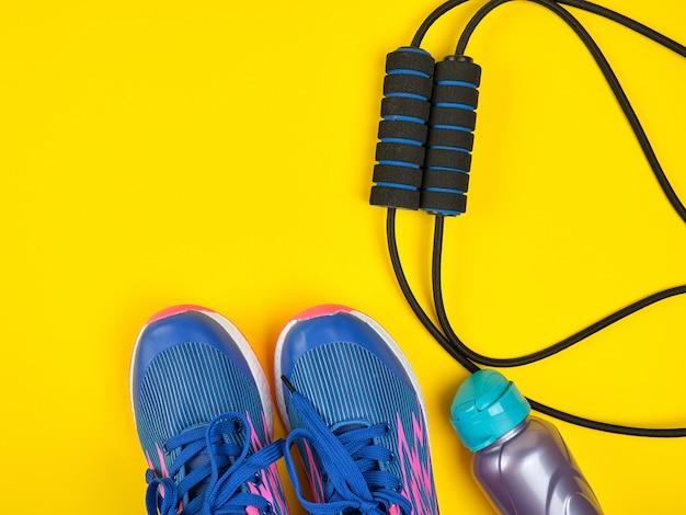 Sportexpander en waterfles en blauwe tennisschoenen op een gele achtergrond