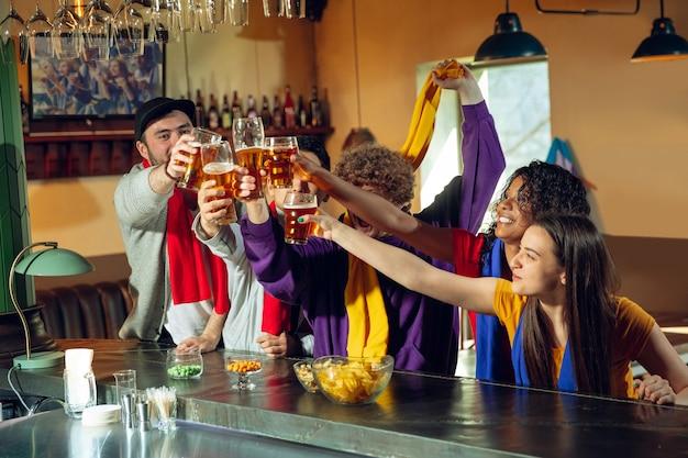 Sportfans juichen bij bar, pub en bier drinken terwijl kampioenschap, competitie gaat. multi-etnische groep vrienden.