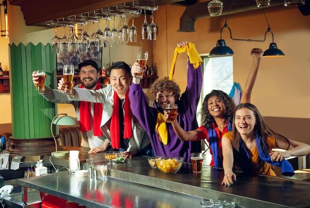 Sportfans juichen in de bar, pub en drinken bier terwijl ze naar een sportwedstrijd kijken.