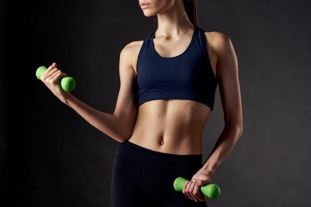 Sportfiguur van een vrouw met halters in handen oefent motivatie donkere achtergrond uit