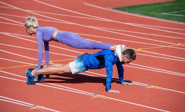 Sportfitness man en vrouw die samen trainen staan in de plank en duwen omhoog op de buitenrenbaan van het stadion met sportkleding, een gezonde levensstijl.