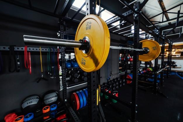 Sporthalter met gele gewichten in focus interieur van een stedelijke sportschool met apparatuur