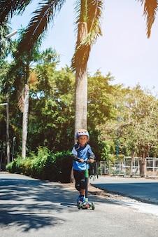 Sporthobby en recreatie op vakanties. vrolijke jeugd jongen rijdt op een scooter en geniet van zijn vakantie op de speelplaats buiten.