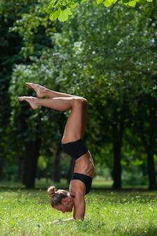 Sportief acrobaatmeisje dat zich op haar handen bevindt, voert een acrobatisch element uit