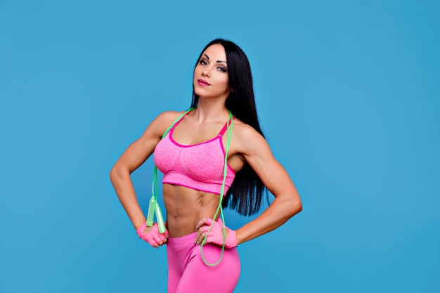 Sportief donkerbruin meisje in de roze sportkleding met touwtjespringen
