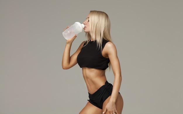 Sportief gespierde vrouw drinkwater, geïsoleerd tegen een grijze achtergrond